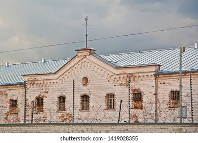 Criminal prison, white building with grilles and iron fences. Latvia, Daugavpils, 2019.
