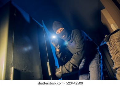 the criminal thief opens the safe in the dark night