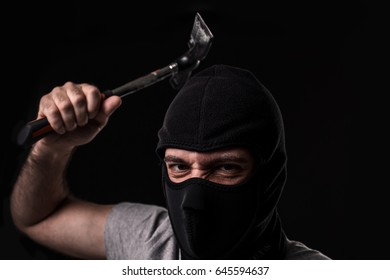 Criminal in T-shirt and balaclava with hammer