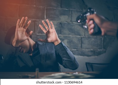 Criminals are aiming at young businessman. Dollar banknotes USD and bullets on the table, The young man hand show signs of surrender and looks scared, concept blackmail, extortion of businesses.
