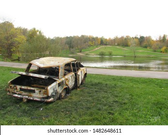 Criminals burned the car and left at a river. Burnt car on the grass by the pond. Damaged and abandoned vehicle.