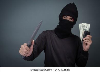 Criminals wear black masks, hold dark and bank cards on a gray background.