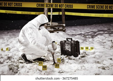 Criminologist collecting evidences on frozen winter location of crime