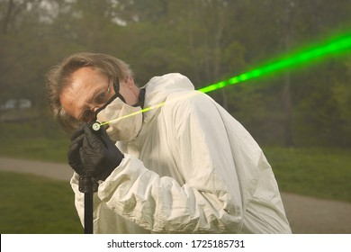Criminologist technician in protective suit and mask working with ballistics laser