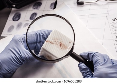 Criminology expert through a magnifying glass looking at evidence