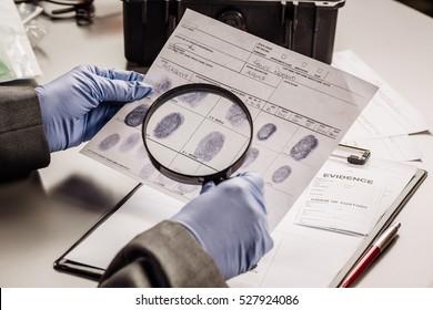 Criminology expert through a magnifying glass looking at a fingerprint