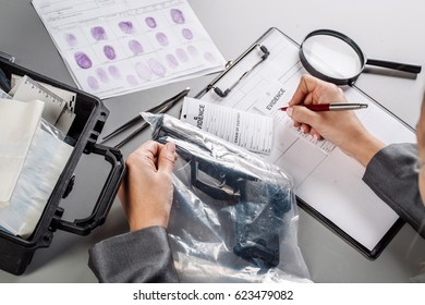 Criminology expert through a magnifying glass looking at a evidence
