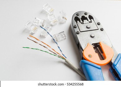 Crimper, transparent connectors and ethernet cable on white background