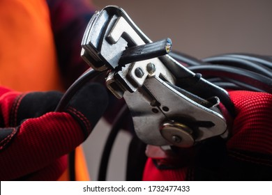 Crimping tool for wires. Crimper close-up. A person is holding a device for crimping wires. Equipment for an electrician.
