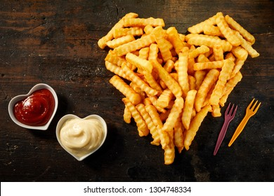 Crinkle cut crispy deep fried Pommes Frites arranged in a heart shape on wood with matching bowls of ketchup and mayonnaise viewed from above