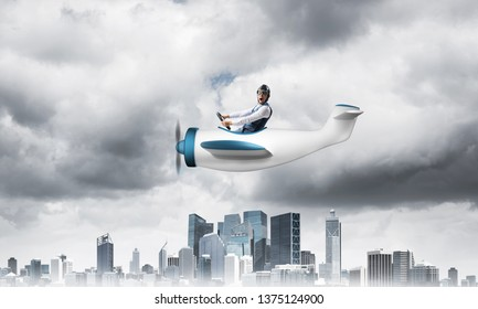 Crisis management and control in difficult situation concept. Businessman in aviator hat driving propeller plane in storm. Pilot flying in small airplane. Megalopolis panorama with dramatic sky.