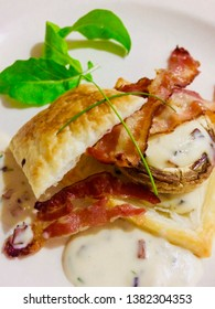 Crisp bacon and mushroom vol au vent (pastry) with a white wine cream sauce, snipped chives and rocket leaf an ideal starter or light meal