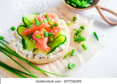 Crisp bread healthy snack with salmon, cottage cheese, cucumber stripes, scallion and sea salt. Easy breakfast concept close-up with copy space.
