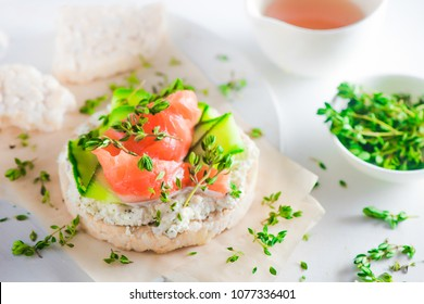 Crisp bread healthy snack with salmon, cottage cheese, cucumber stripes, thyme and pepper. Easy breakfast concept close-up with copy space.