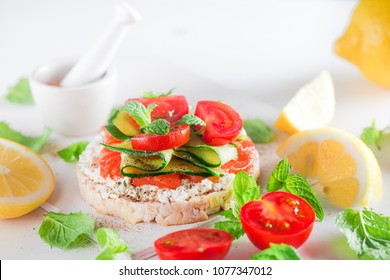 Crisp bread healthy snack with salmon, cottage cheese, cucumber stripes, fresh cherry tomatoes, mint, lemon juice, pepper. Easy breakfast close-up on a white background with copy space.
