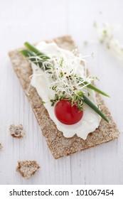 crisp bread sandwich with cream cheese, broccoli sprouts, tomato and chive
