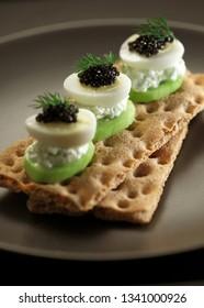 Crisp bread toast with quail egg and black caviar