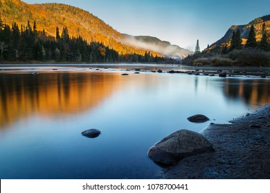 A crisp and clear fall morning along the river at Jacques Cartier National Park in Quebec, Canada. The rising sun lights up the hill covered by colorful maple trees.