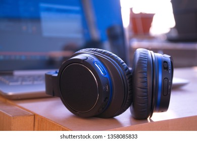 Crisp close-up of wireless headset / headphones with laptop in background and strong bokeh