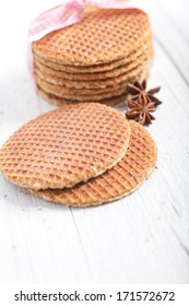 Crisp golden waffles with star anise spice lying on a rustic white wooden background ready to be prepared for a festive dessert