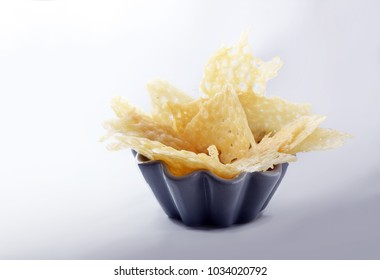 crisp parmesan cheese chips, finger food party snack or appetizer in a bowl on a light gray background, copy space, selected focus, narrow depth of field