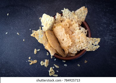 crisp parmesan cheese chips, homemade party snack in a bowl on a dark slate background, high angle view from above, copy space