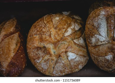 Crisp round loaf of bread on display at a french rustic bakery.