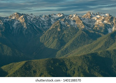 Crisp Snow Covered Mountain Range Over Green Forest and Mountains