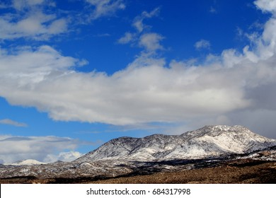 Crisp sunny winter's day with huge puffy white clouds against a deep blue sky with snow covered Catalina mountains in Tucson Arizona