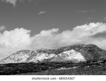 Crisp winter's day with huge puffy white monsoon clouds over the snow covered Catalina mountains in the Tucson Arizona desert black and white