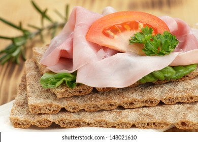Crispbread with ham and tomato on wooden board