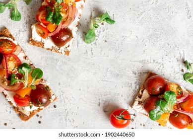 Crispbreads with feta, colorful cherry tomatoes, onions, and herbs. Toast with cream cheese and tomatoes on a gray background top view. Free space for text. Tasty breakfast or snack. Food background - Shutterstock ID 1902440650