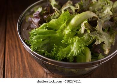 Crisphead lettuce in a bowl on wooden table