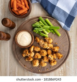 Crispy air fried cauliflower florets and ranch dip with carrots and celery on a wooden tray.  Overhead view