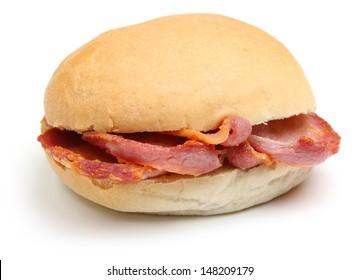 Crispy bacon in a soft white bread roll or bap.