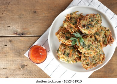 Crispy Bakwan Sayur, or heci, Bala-Bala or Vegetables Fritter, Indonesian snack with carrot, cabbage and flour as the main ingredients in white plate serve with sauce selective focus.