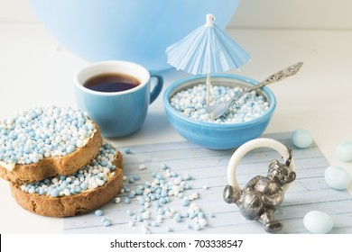 crispy biscuits, cup of tea, bowl with Dutch blue and white sugared aniseed balls, and silver bear rattle for celebration the birth of a baby boy
