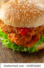 crispy, breaded chicken burger with mozzarella cheese standing on wooden cutting board