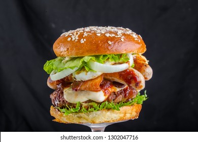 Crispy burger with bread, sausage, sausages, tomatoes sauce, flowing mozzarella melted fried yellow cheese, flakes seeds, juicy meat, pork meat steak, tomatoes, lettuce leaves, black background