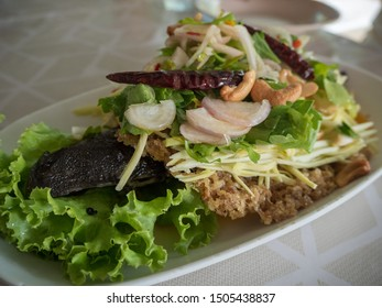 Crispy catfish spicy salad with green mango, Thai food, Crispy catfish salad with green mango and vegetable , served with salad and lettuce.