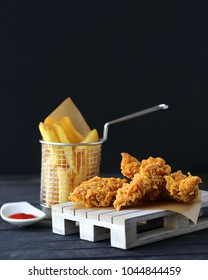 Crispy chicken strips with delish spicy ketchup in ramekin and french fries in a fancy support, wooden plate. Dark background. Junk fast food concept. Selective focus. Copy space for text