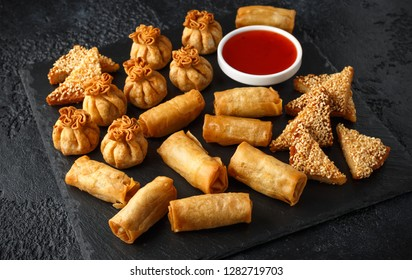 Crispy Chicken wontons, vegetable spring rolls and prawn toasts with sweet chilli sauce. chinese selection. fast food.