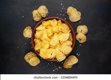 Crispy chips in a bowl on a stone background