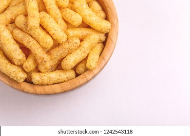 Crispy corn sticks in wooden bowl on light background. Snacks for watching movies. Copy space