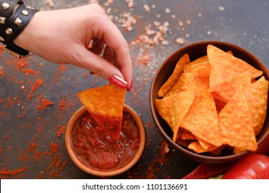 crispy crunchy tortilla nacho chips are a great party munchies. delicious food snack. woman hand dipping crunchy spicy triangular crisps in salsa tomato sauce
