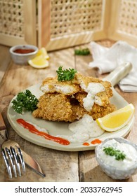 Crispy dory fish, cut in fillet and fried with four and oat, serving with tartar and tomato sauce on wooden table. Southeast Asia food and recipe, Indonesian food and cuisine.