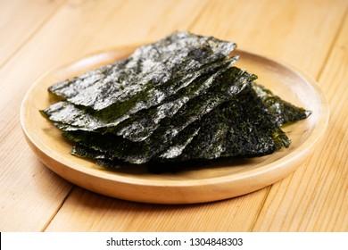 Crispy dried seaweed, Nori sheet, on wooden dish