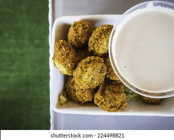 Crispy Falafels in a white bowl with a cup of tahini sauce - down view