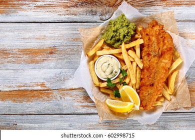 crispy fish and chips - fried cod, french fries, lemon slices, tartar sauce and mashed peas on plate on paper on old wooden tabletop, authentic british recipe, view from above, blank space left