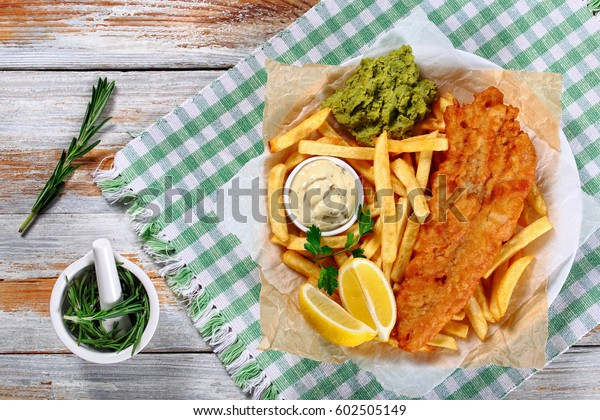 crispy fish and chips - fried cod, french fries, lemon slices, tartar sauce and mashed peas on plate on paper on old wooden table with rosemary in mortar, authentic recipe, view from above